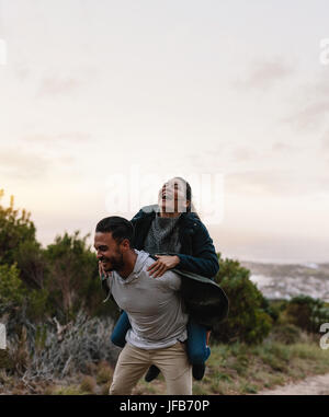 Smiling young man carrying his girlfriend on back. Couple enjoying piggyback ride in countryside. - Stock Photo
