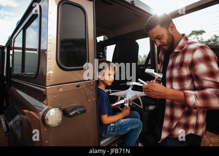 Shot of father and son at the back of their car setting up a drone to fly. Young man and son assembling a drone - Stock Photo