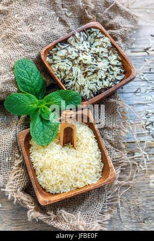 Different varieties of rice in wooden bowls. - Stock Photo