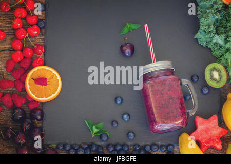 Fresh smoothie berry healthy drink in glass jar with igredients on black stone, retro toned - Stock Photo