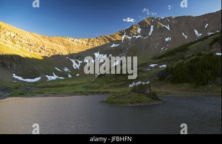 Upper Jubilee Tarn at top of alpine valley between Mounts Allan and Collembola in Kananaskis Country, Canadian Rocky - Stock Photo