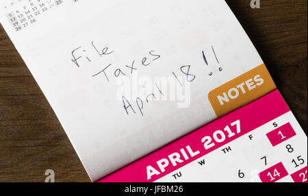 Note written on calendar for tax day - Stock Photo