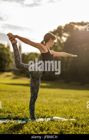 Young attractive woman doing dancers yoga pose outdoors on field - Stock Photo