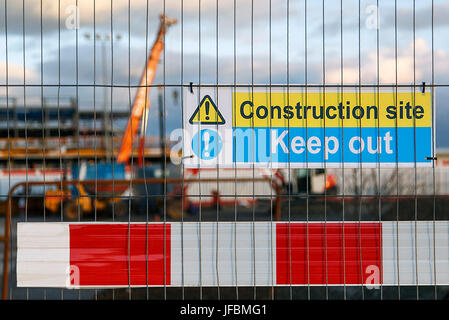 Construction site warning signs in yellow and blue instructing people to Keep Out