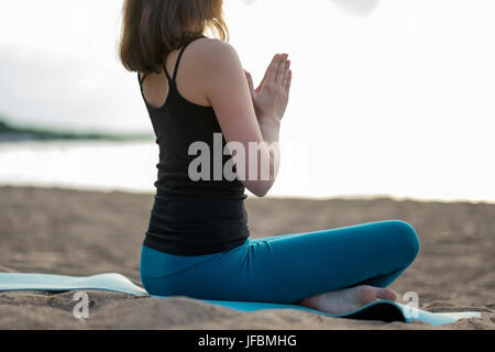 Woman doing yoga - meditating and relaxing in Padmasana Lotus Pose - Stock Photo