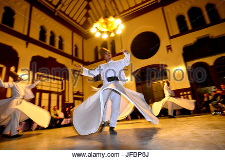 Members of the Mevlevi Sufi Order, whirling dervishes perform at the Sirkeci Central Train Station. - Stock Photo