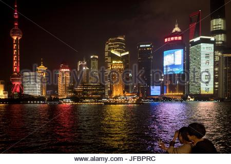 People taking a selfie on a cell phone on the Bund promenade. - Stock Photo