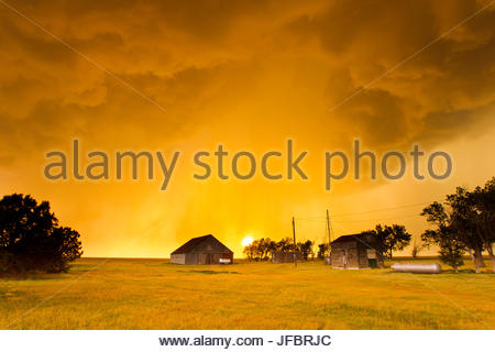 Orange illuminated sky as sun sets behind a supercell thunderstorm and shines through a rain shaft near Campo, Colorado. - Stock Photo