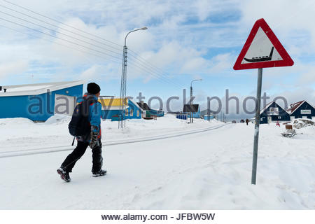 A kid walking home on a snow-covered street passing a dog sled crossing warning sign. - Stock Photo