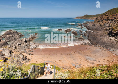 17 June 2017: Combesgate Beach, Woolacombe, North Devon, England, UK - A man and his dof leaving the beach. - Stock Photo