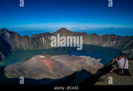 Tourist sitting on the rim of the crater of Gunung Rinjani volcano in Lombok island,  Indonesia - Stock Photo