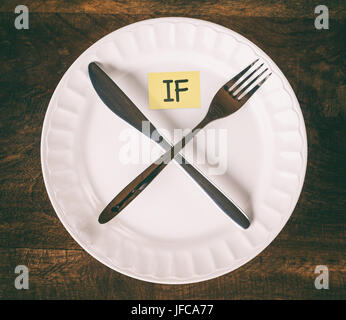 Intermittent fasting concept with knife and fork showing cross symbol on white plate with sticky note that reads IF, top view, vintage effect