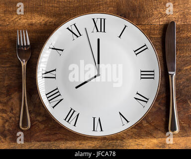 Eight hour feeding window concept or breakfast time with clock on plate and knife and fork on wooden table, overhead view