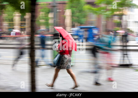 Belgrade, Serbia - May 5, 2017: Blurry woman under umbrella walking on the city street on a rainy spring day - Stock Photo