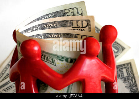 Red figures surrounding American dollar notes - Stock Photo