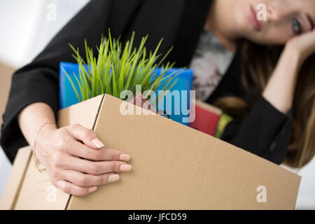 Young dismissed female worker in office holding carton box with her belongings. Getting fired concept. - Stock Photo