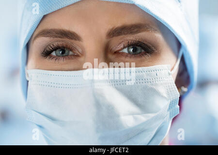 Close up portrait of adult female surgeon doctor wearing protective mask and cap. Surgeon in operation theatre. - Stock Photo