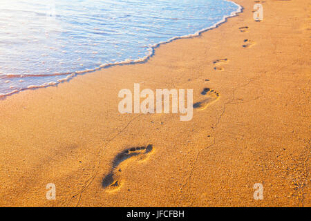 beach, wave and footprints at sunset time - Stock Photo