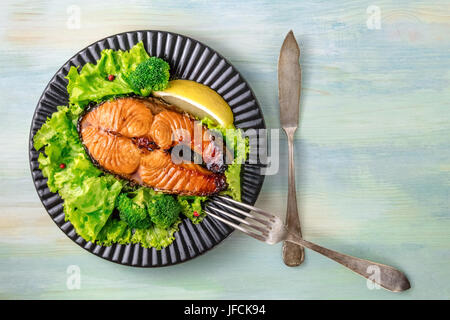 An overhead photo of a grilled salmon steak, with fresh green salad, broccoli sprouts, a slice of lemon, and pink - Stock Photo