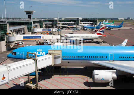 AMSTERDAM - JUNE 27: Various airlines at the gates of Amsterdam Schiphol Airport, Europe's fifth busiest airport, - Stock Photo