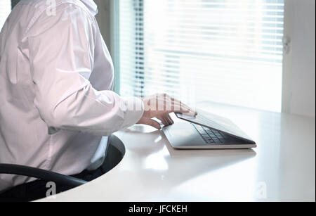 Office worker starting or ending work day by opening or closing laptop lid. Going home after job done or coming - Stock Photo
