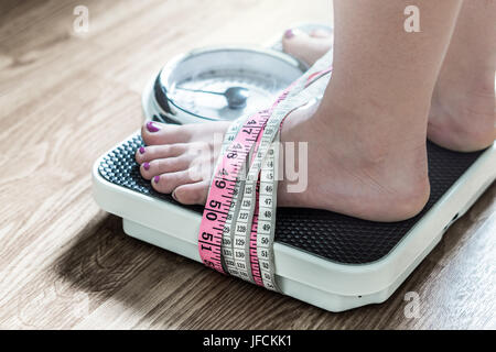 Feet tied up with measuring tape to a weight scale. Addiction and obsession to weight loss. Anorexia and eating - Stock Photo