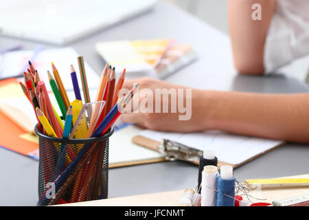 Close-up view colourful pencils and threads with  female dressmaker working at background - Stock Photo
