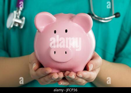 Female medicine doctor wearing green uniform holding funny pink piggy bank. Doctor hands close up. Medical service - Stock Photo