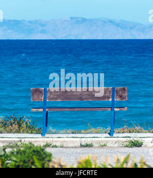 Wooden bench overlooking the sea and mountains - Stock Photo