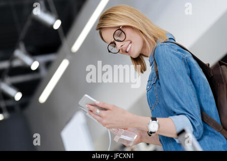 I like this one a lot. Cheerful young lady wearing glasses and a black wrist watch beaming while trying out a mockup - Stock Photo