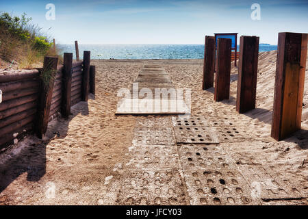 Entrance walkway to the beach at Baltic Sea on Hel Peninsula in Poland, reinforced with wooden beams and concrete - Stock Photo