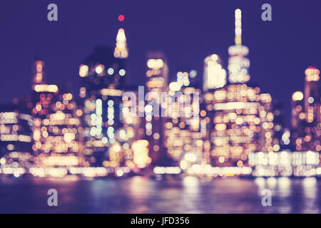 Blurred vintage toned Manhattan waterfront skyline at night, New York City, USA. - Stock Photo