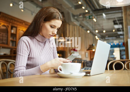 Beautiful brunette using laptop in cafe. Blogger work concept - Stock Photo