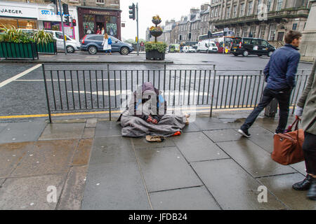 Edinburgh, UK: May 27, 2016: A beggar sits in the rain on a busy junction in Edinburgh. It is raining and he is - Stock Photo