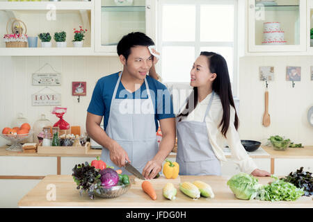Asian beautiful young wife helping husband dry sweat off his face in kitchen at home. Happy love couple concept.