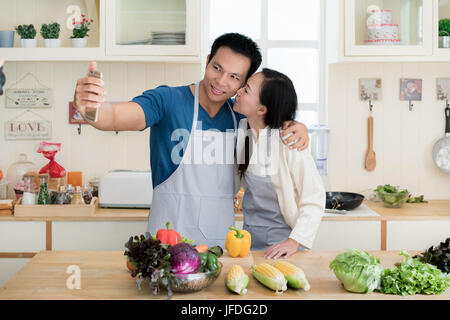Asian handsome guy is smiling and cooking in kitchen while doing selfie using smartphone at home. Happy love couple - Stock Photo