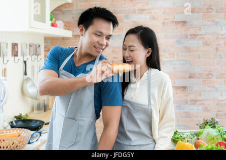 Asian beautiful young couple is feeding bread smiling while cooking in kitchen at home. Happy love couple in home. - Stock Photo