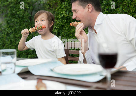 Father with little bcute boy eating barbecue in family lunch time at home. - Stock Photo
