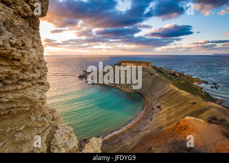 Mgarr, Malta - Panorama of Gnejna bay, the most beautiful beach in Malta at sunset with beautiful colorful sky and - Stock Photo