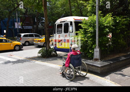 Old woman in a wheelchair waiting for a ride home from the hospital, taipei, Taiwan. - Stock Photo