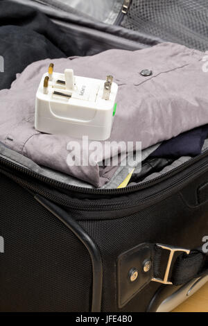 Travel power adapter with connectors for european, UK, and US power plugs on packed suitcase with clothings - travel - Stock Photo