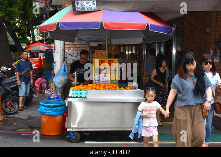 Freshly squeezed orange juice stand just 10 meters from Mackey Hospital in Taipei, taiwan. Super hot day - Stock Photo