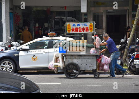 A food stand person pushes his cart past a police station near Mackay Hospital. Taipei, Taiwan. - Stock Photo