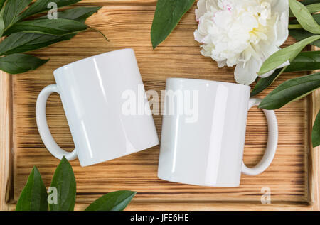 Two white mugs, cups wedding mockup. Peony, green leaves, wooden background. Summer gifts, boho style - Stock Photo