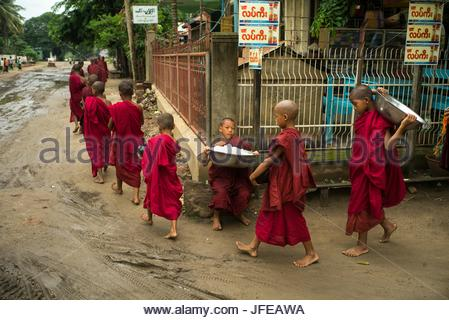 Child monks walk in a line, some carrying rice bowls. - Stock Photo
