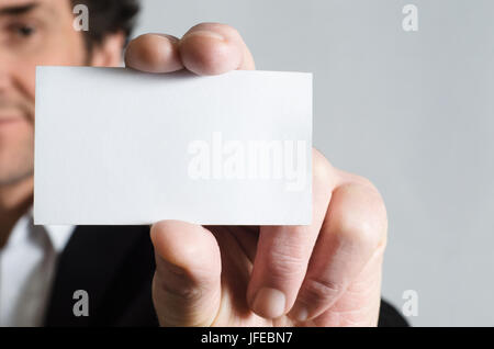 A man in a black suit with white shirt holding up a blank business card to display to viewer. - Stock Photo