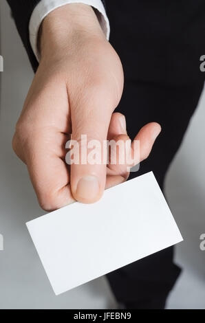 Close up of the hand of a man in a suit, reaching forward holding a blank business card facing upwards towards the - Stock Photo