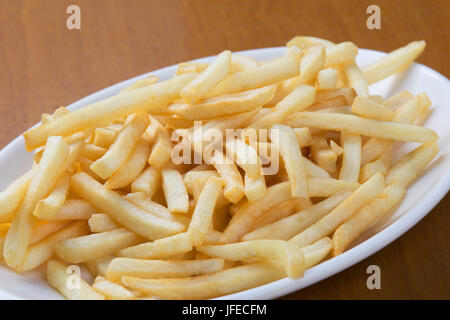 A plate full of delicious shoestring style french fries - Stock Photo