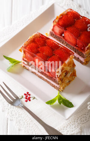 A delicious strawberry chocolate cake with jelly closeup on a plate on a table. vertical - Stock Photo