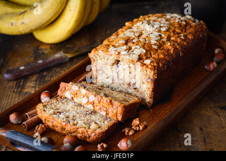 Banana bread with walnuts, cinnamon and chocolate chips on wooden tray. Closeup view, selective focus - Stock Photo